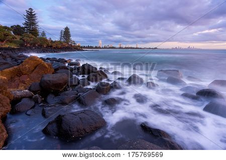 Moody sunrise at Burleigh Heads on the Gold Coast, Queensland, with Surfer's Paradise visible on the distant horizon.