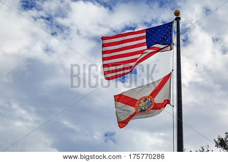 Florida state flag with american flag with cloudy sky background