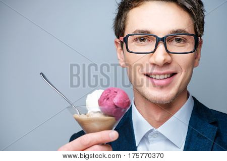 Handsome young man with glasses, a blue jacket and white shirt with multi-colored ice-cream in a transparent cup and teaspoon in the studio