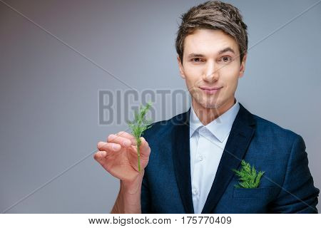 beautiful young attractive man in a blue business suit and white shirt in a studio with green fennel in hand and in your pocket. With a raised eyebrow and herbs between your fingers.