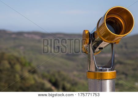 Coin operated telescope in the foreground on a terrace
