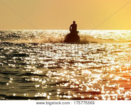 Silhouette of strong man jumps on the jet ski above the water at sunset
