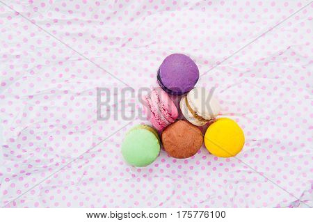 Multicolored Cake Macaron Or Macaroons In The Triangle Form On The White With Pink Peas Background.