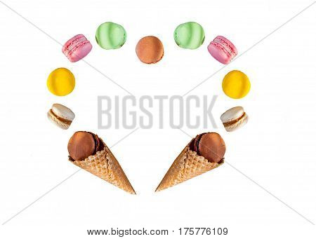 Multicolored Cake Macaron Or Macaroons And Waffle Cones In The Form Of A Heart Frame On The White Ba