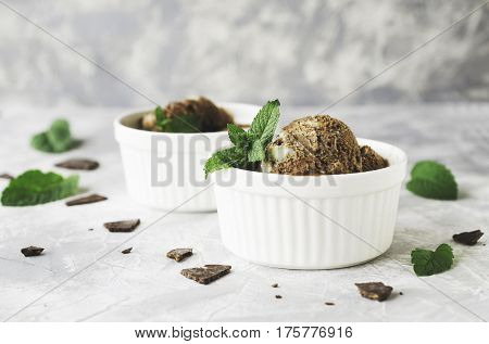 chocolate mint ice cream in white bowls with pieces of chocolate and mint leaves on a marble table, selective focus, high resolution