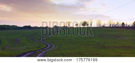 Dirt road among meadows with trees in the distance at sunset