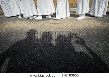 Tourist shadows taking photos and enjoying easter traditional procession in bercianos de aliste brotherhood, zamora, Spain