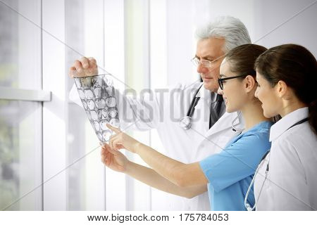 Group of doctors looking at roentgenogram in clinic