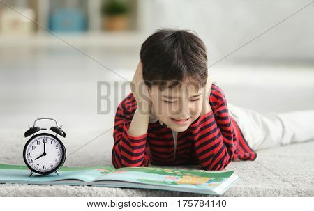 Cute little boy with ringing alarm clock lying on floor at home