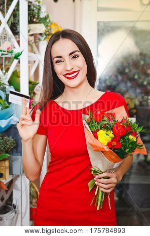 attractive young girl working in a flower shop, credit cards
