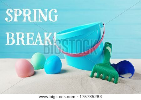 Spring break concept. Colorful Easter eggs and toddler beach kit on sand