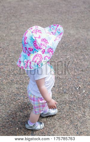 Cute toddler girl playing on the farm in the summer.