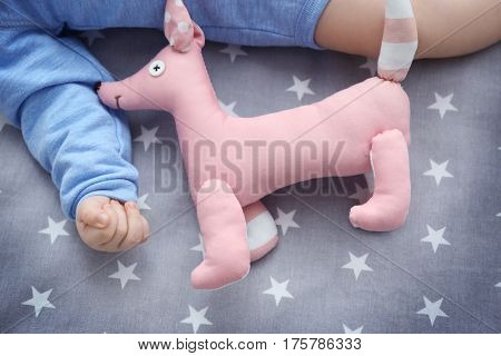 Cute little baby with dog toy lying in cradle at home