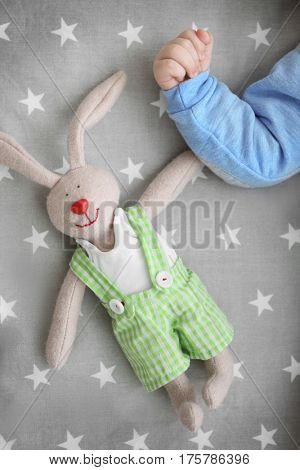 Hand of cute little baby with bunny toy lying in cradle at home