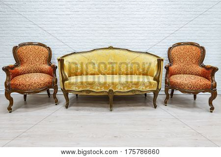 Old vintage luxury sofa and pair of armchairs on the white wall background.