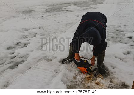 Man Cutting Chainsaw Shell In Ice