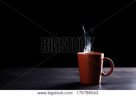 Cup with hot liquid on table against dark background