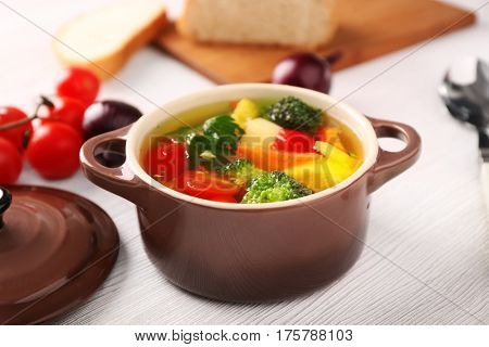 Saucepan with delicious soup and vegetables on kitchen table