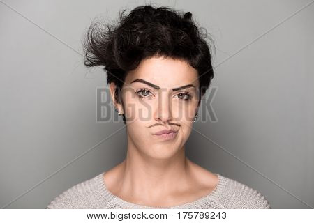 Woman with Drawn Mustaches on Gray Background Making Face