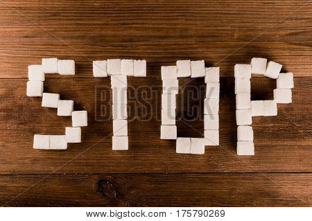 Diabetes. Word Stop from sugar cubes with syringe.