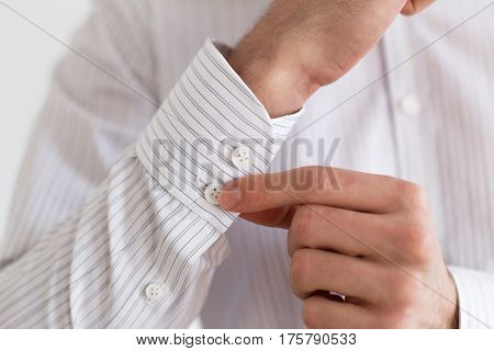 Sleeve of a white shirt. Buttons on Cuffs. close up view