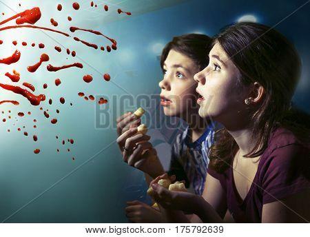 teens boy and girl watching horror movie film with pop corn blood splash