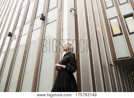 Wide angle view, woman in long black dress, building