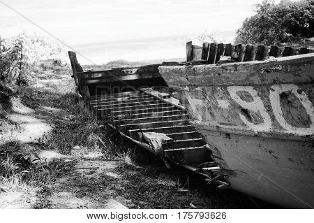 Dilapidated boat on the sea shore. Black and white photo.