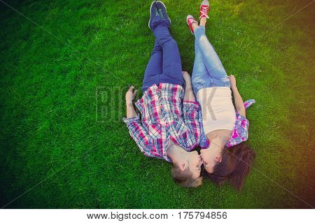 beautiful cute couple lying on the field and kissing holding hands close up