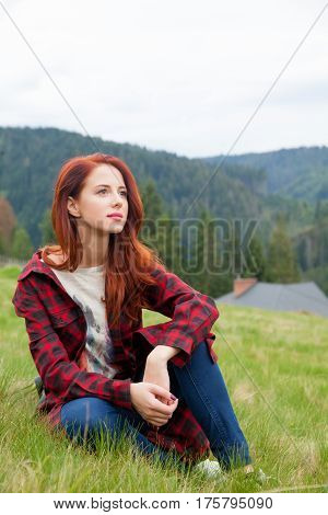 Beautiful Young Woman Sitting In The Field And Relaxing On The Wonderful Sky And Mountain Background