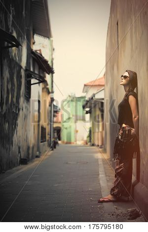 beautiful young woman standing near wall in the one of streets of Sri Lanka