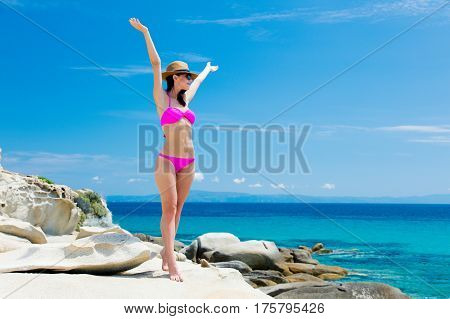 beautiful young woman standing on the wonderful stone coast in greece in swimsuit