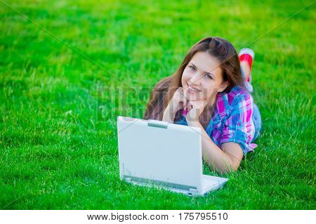beautiful young girl lying on the field with laptop on the wonderful grass background