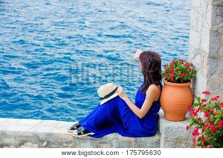 Photo Of Beautiful Young Woman Sitting Near Ot With Flowers On The Sea Background