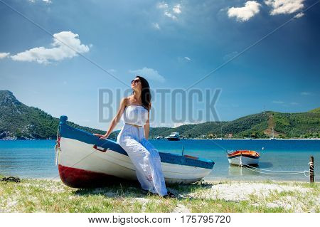 beautiful young woman sitting on the wonderful boat on the coast in Greece
