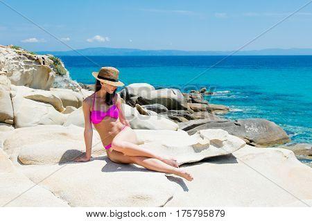 Beautiful Young Woman Sitting On The Wonderful Stone Coast In Greece In Swimsuit