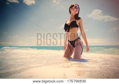 beautiful young woman sitting on the wonderful sand beach in greece