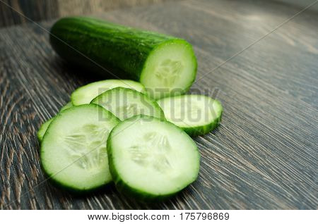 Heap of fresh sliced Cucumbers on an wooden table.