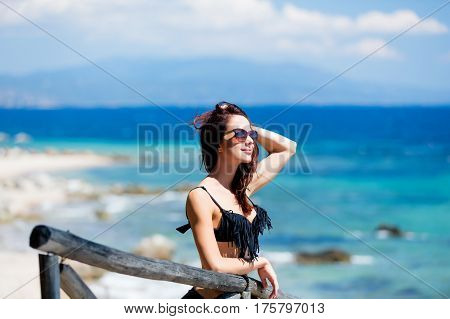 beautiful young woman standing near wooden fence and looking at the sea in Greece