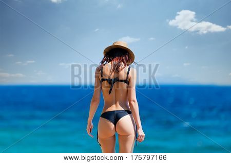 Beautiful Young Woman Standing On The Coast And Looking At The Sea In Greece