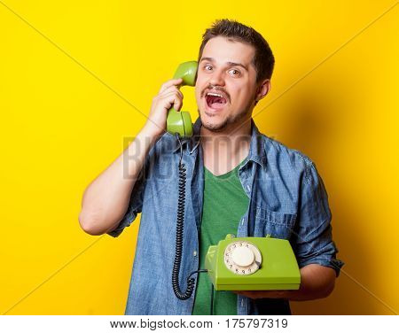 handsome young man holding green retro phone on the wonderful yellow background
