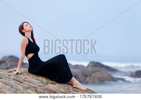 beautiful young woman sitting on the stone coast in sunny Sri Lanka