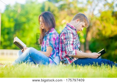 beautiful cute couple sitting on the field and reading their books