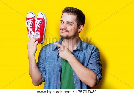 handsome young man holding red gumshoes on the wonderful yellow background