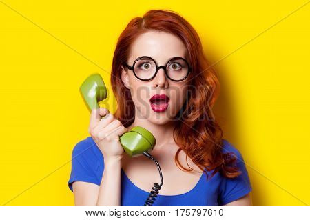 Beautiful Surprised Young Woman With Retro Phone On The Wonderful Yellow Background