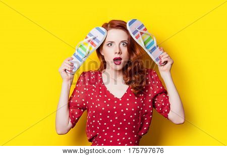 Beautiful Surprised Young Woman With Colorful Sandals On The Wonderful Yellow Background
