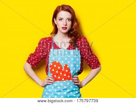 Beautiful Young Woman In Pinafore With Potholder On The Wonderful Yellow Background