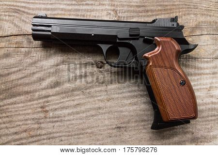 Pistol on a wood background. Handle right.