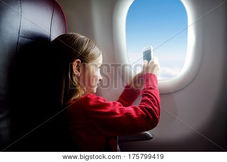 Adorable Little Girl Traveling By An Airplane. Child Sitting By Aircraft Window Taking Pictures Of T