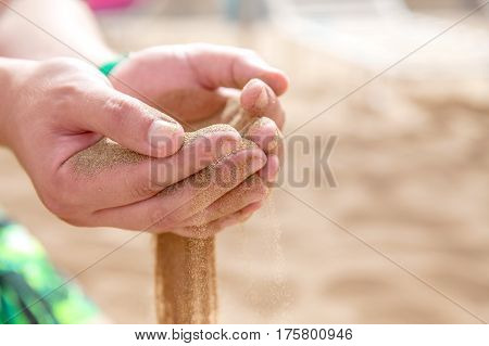 Mans Hands strew a sand running , Fingers